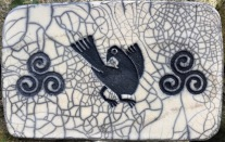 plaque sous plat en raku avec triskell et oiseau