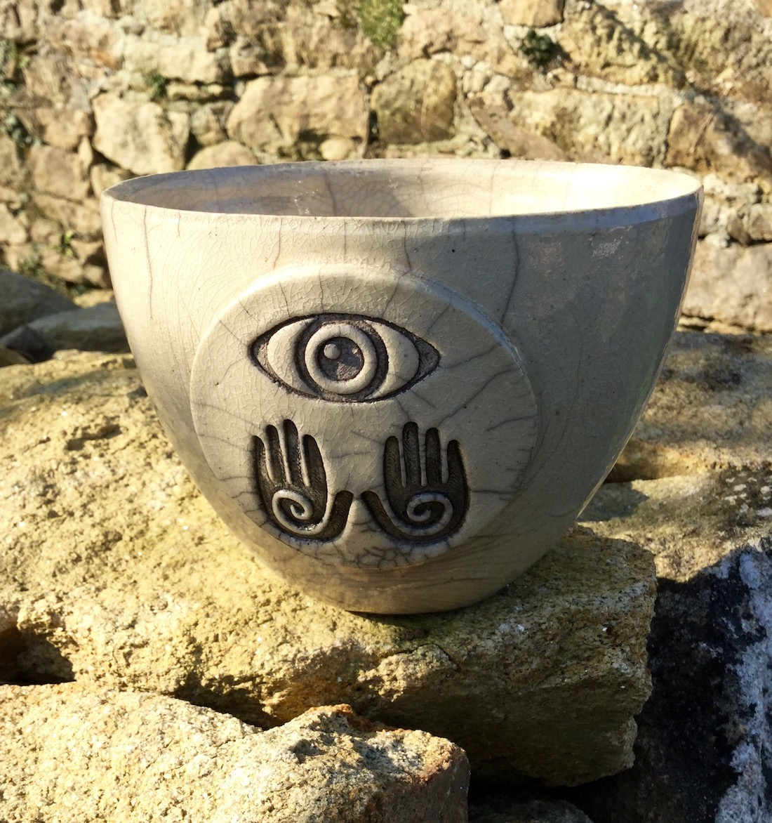 grand bol raku avec motif oeil et mains